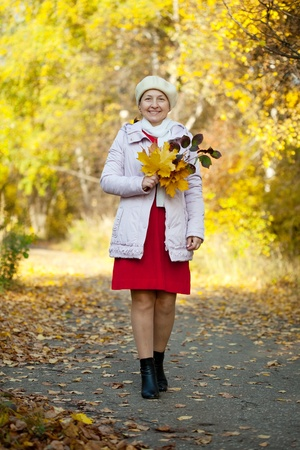 Full length shot of happy mature woman  in autumn park photo