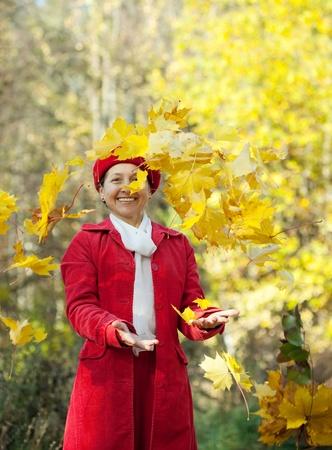 happy seasonable: Happy mature woman throwing yellow maple leaves  in autumn  Stock Photo