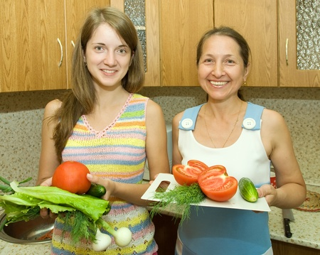 mother and daughter in the kitchen with some vegetables photo