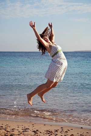 splutter: Young  woman jumps  on  sea  beach