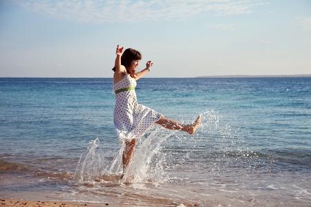 splutter: Happy  woman plays  at sea  coast