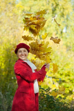 happy seasonable: Happy mature woman throwing yellow maple leaves in the air in autumn  Stock Photo