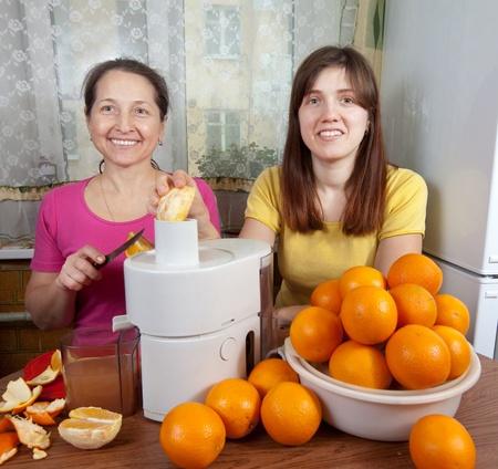 Two women  making fresh orange juice in home kitchen photo