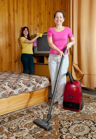 vaccuum: Women are cleans with vacuum cleaner in home