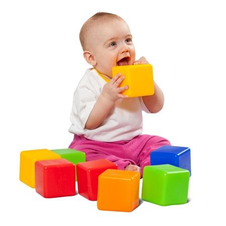 Bonne petite fille joue avec des blocs de jouet sur fond blanc