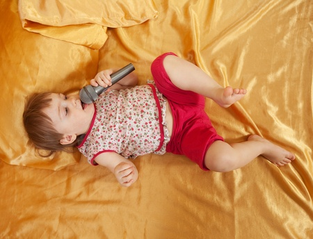 Toddler  sings into a microphone lying on the bed photo