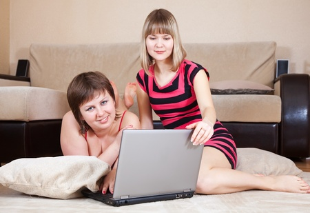 Two happy women using laptop in home photo