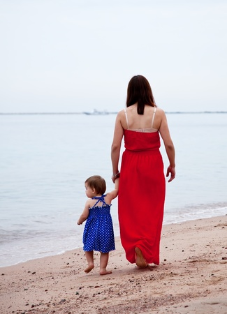 Rear view of  mother with  toddler walking  on sand beach Stock Photo - 13086840