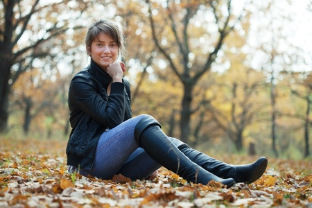 Girl in jacket and black knee-high boots at autumn park  photo
