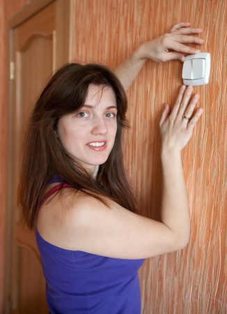 Young woman with light switch in home photo