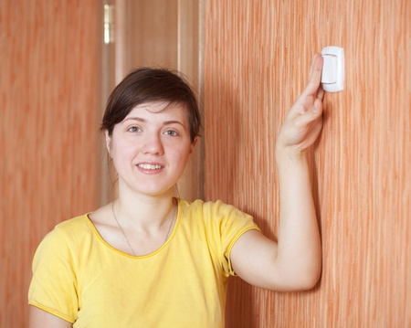 Young woman turning off the light switch in home Stock Photo - 13119915