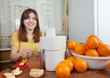 young woman making fresh orange juice in her kitchen photo