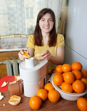 smiling young  woman adding orange to juicer in her kitchen photo