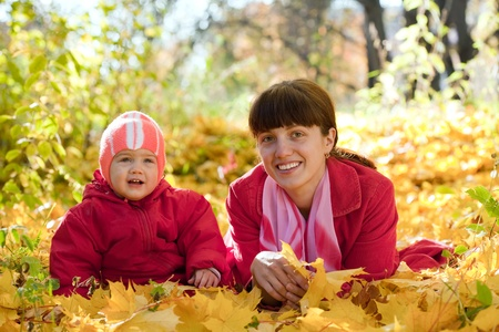 Mother and   baby laying on maple leaves in autumn park Stock Photo - 13151759
