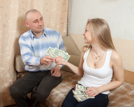 The wife gives her husband the money at home Stock Photo - 13151734