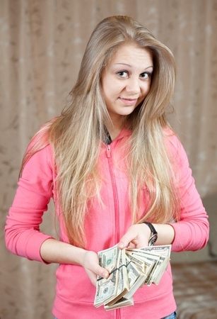 happy casual girl with bundles of US dollars  in home interior photo