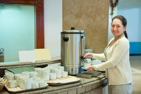 Woman pours tea from  electric water boiler photo