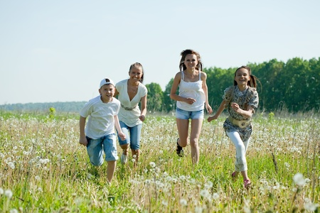 Two happy  women with teens running in grass photo