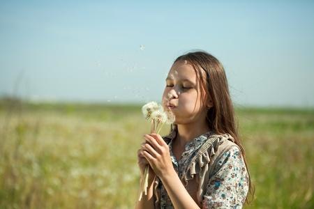 Teenager girl blowing seeds of dandelion flower photo