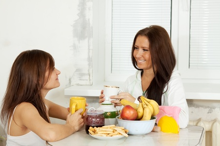 Two smiling women have tea in kitchen photo