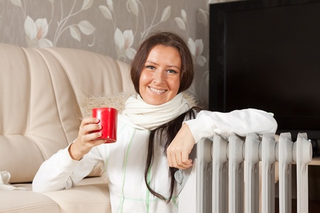 oil heater:  smiling woman  with red cup near oil heater