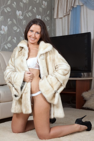 woman in fur coat: Sexy woman in fur coat  at home interior Stock Photo