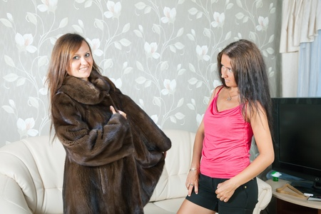 Woman  make boast of fur coat  in home Stock Photo