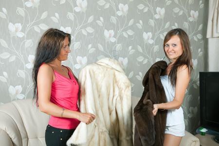 boast: Le donne fanno vanto di pellicce in casa Archivio Fotografico