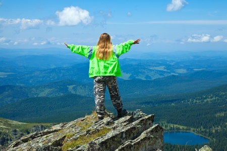 happy woman standing on  rock with raised hands  at mountain peak photo