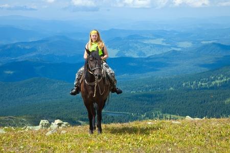 Female rider on horseback at mountains Stock Photo - 13201124