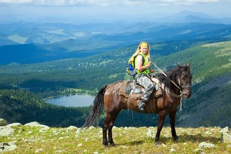 Female rider on horseback at mountains. Karakol lakes, Altai photo