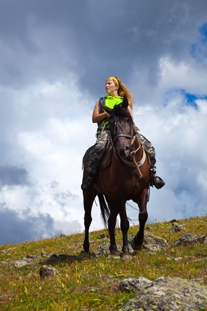 Cavaliere femminile a cavallo alle montagne photo