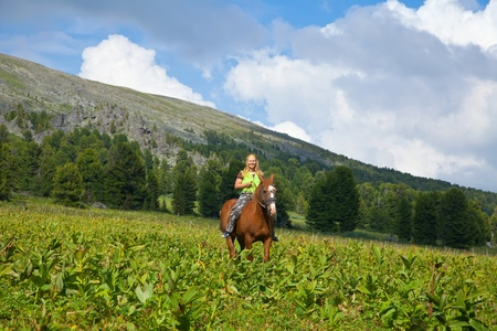 Happy girl riding a horse bareback at mountains  photo