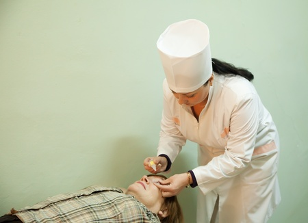 Ophthalmologist measures the  ocular tension in patients photo