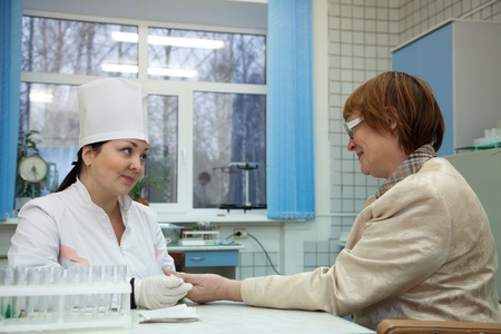 Nurse taking blood sample  from patient in clinic Stock Photo - 13201275