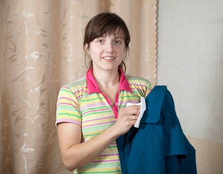 kerseymere: Woman cleaning coat  with washrag  at home