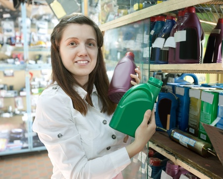woman holds  motor oil in  auto spare parts store photo
