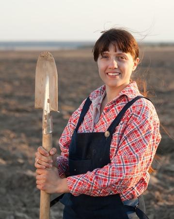 plowed field: Female farmer  with spade in plowed field