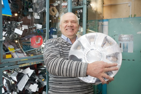 mature man buys  automotive wheel cover in  auto parts store photo