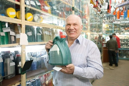 man with canister of motor oil in auto store  photo