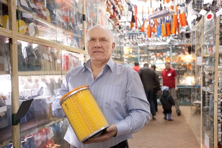 mature man holds  automotive  air filter in  auto parts store photo