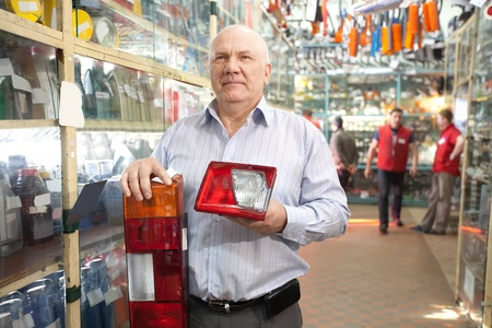 mature man holds  automotive  headlight  in  auto parts store photo
