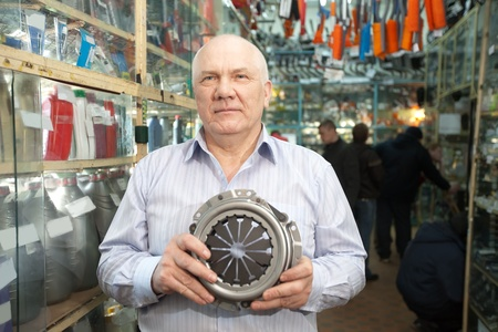 mature man holds  engine clutch  in  auto parts store photo