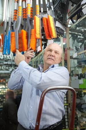 mature man chooses  automotive broom  in  auto parts store photo
