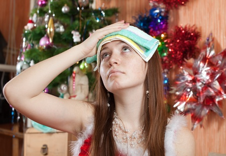 cephalgia: Woman in christmas hat having hangover at home