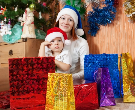 Happy mother and little son  with  Christmas gifts at  home  photo