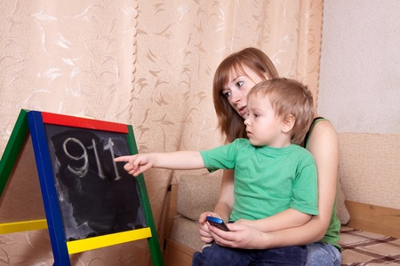 teaches: Mother teaches child to emergency phone numbers Stock Photo