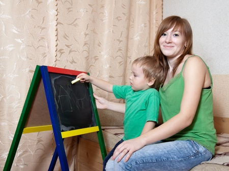 Mother and child draws on the blackboard with chalk Stock Photo - 13306077