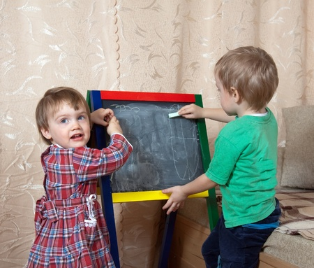 children draws on the blackboard with chalk at home photo