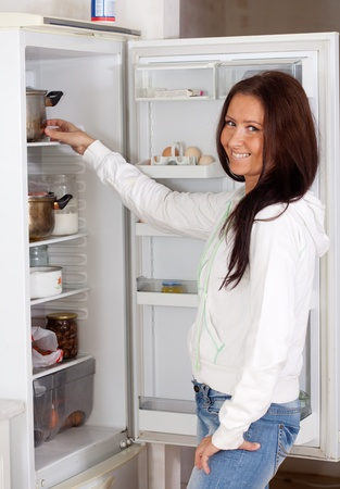Happy woman looking for something in the fridge at home photo